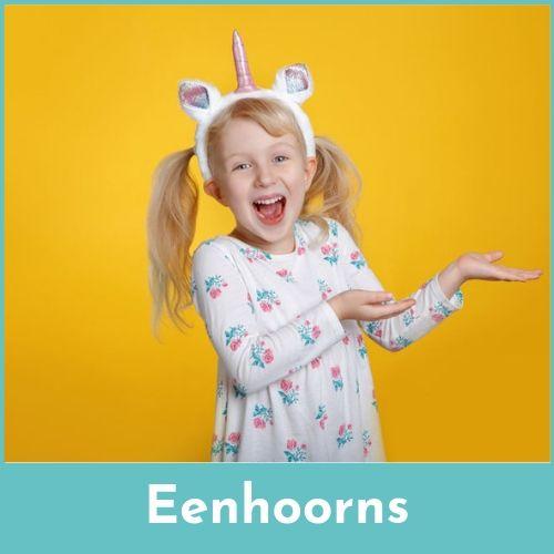 Lachend blond meisje met een eenhoorn haarband tegen een gele achtergrond