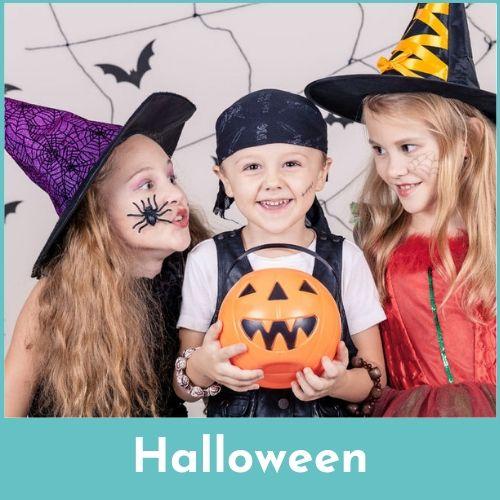 Jongen met zwarte piratenmuts en pompoen in de handen en twee meisjes met een heksenhoed op
