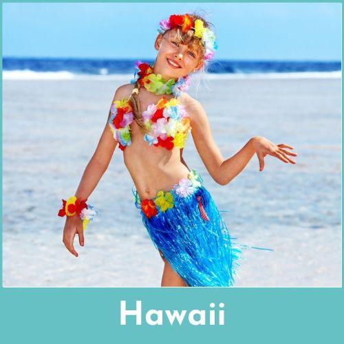 Lachend meisje op het strand met een blauw rieten rokje aan, een bloemenkrans rond de hals en een bloemen haarband in de haren