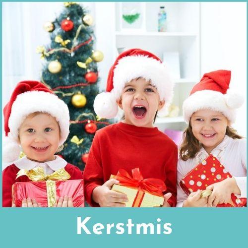 Twee jongens en een meisje met kerstmuts op en cadeautjes in de handen tegen een achtergrond met kerstboom