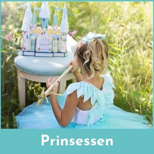 Meisje verkleed als een prinses bij een tafel waarop een speelgoedkasteel staat