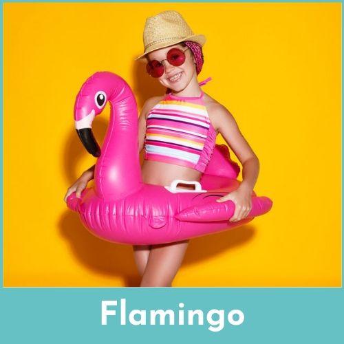 Lachend meisje met een zonnebril op, een rieten hoed op het hoofd in een grote roze zwemband met flamingo tegen een gele achergrond