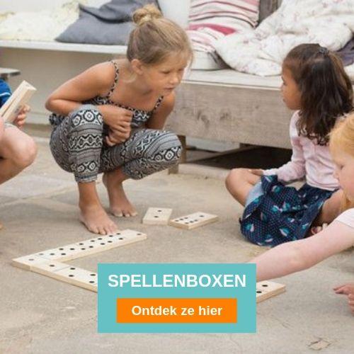twee meisje die op de grond zitten en een mega groot dominospel spelen