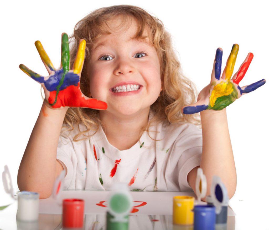 lachend meisje met de handen vol verf tegen een witte achtergrond