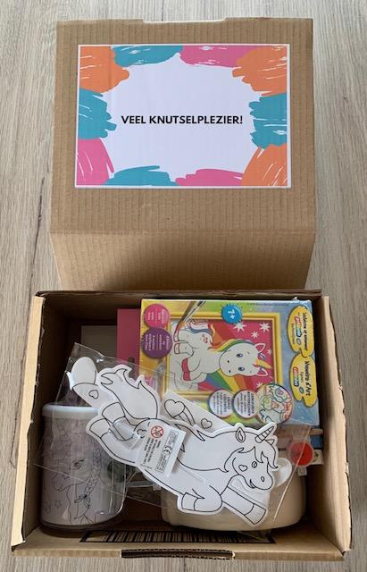 kartonnen doos met knutselmateriaal rond het thema van eenhoorns
