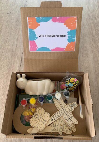 Kartonnen doos met knutselmateriaal in het thema van kleine beestjes